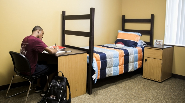 EKU offers housing conducive to study. A seated student doing coursework.