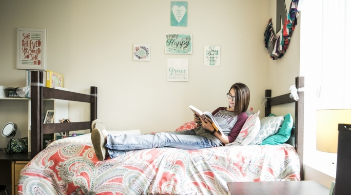 Summer housing options are varied. Here a female student reads on her bed.