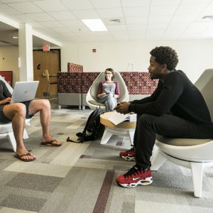 Three EKU students discuss their classes in the North Hall lounge