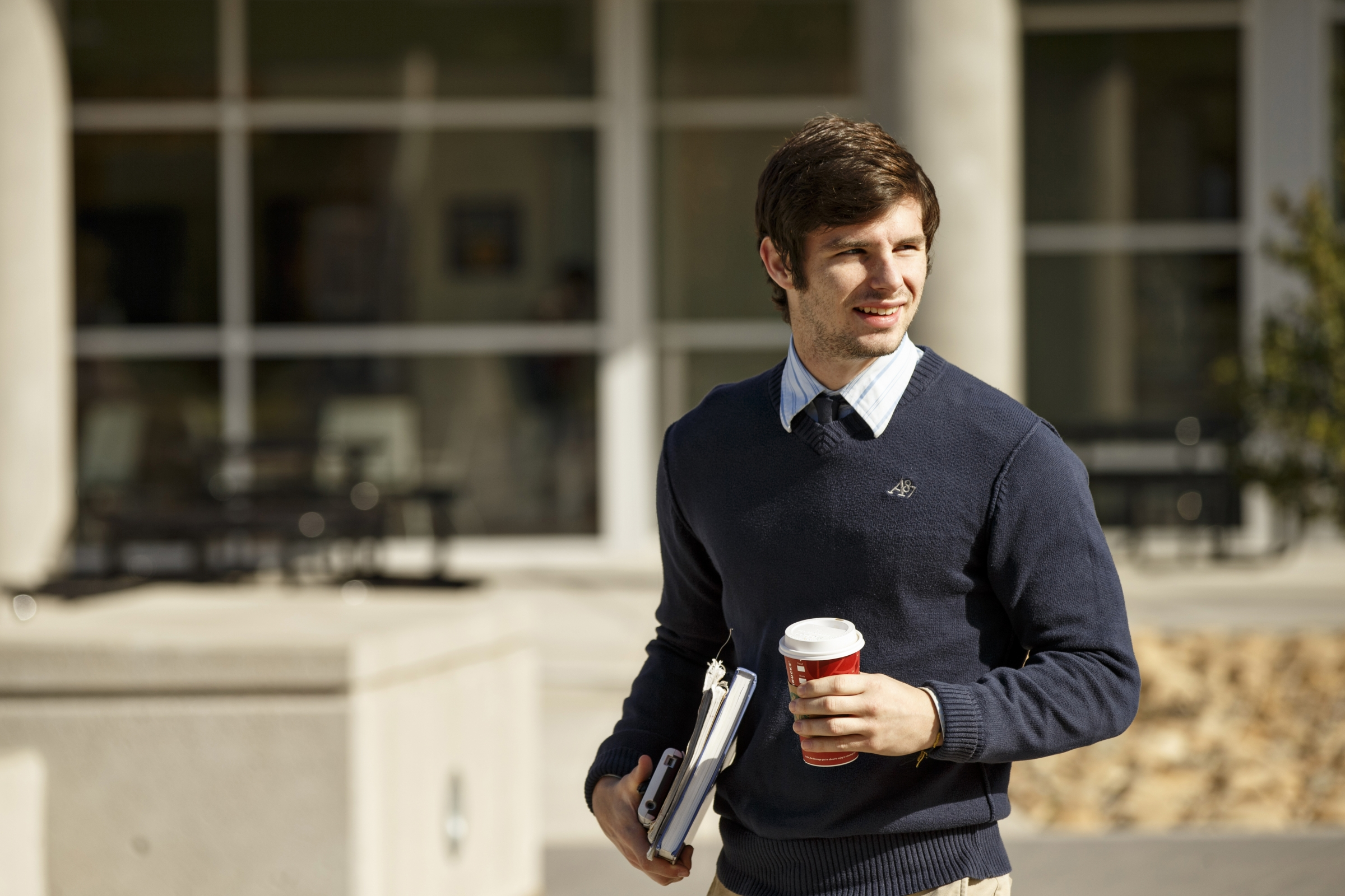 Male student walking with cup of coffee and books in hand